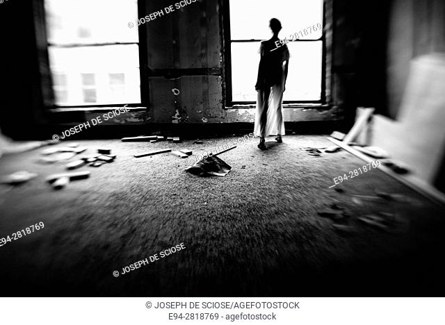A silhouette back view of a young woman dressed in a long white gown looking out of a window in an old building, black & white
