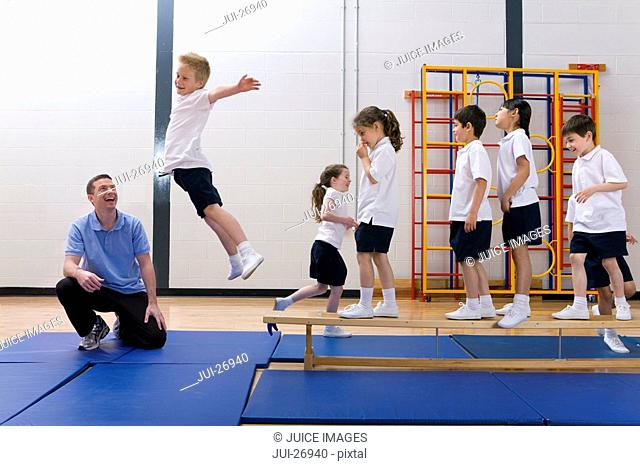Gym teacher watching school boy jump off bench in school gymnasium