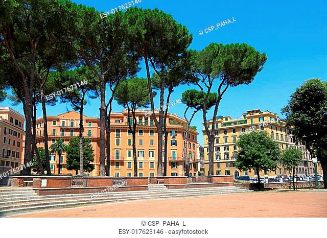 multi-storey yellow houses in Rome, high green trees, blue sky