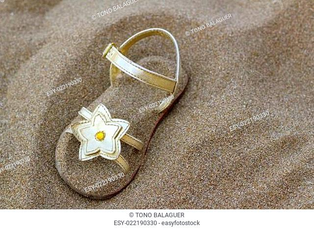 golden star sandal buried in summer beach sand