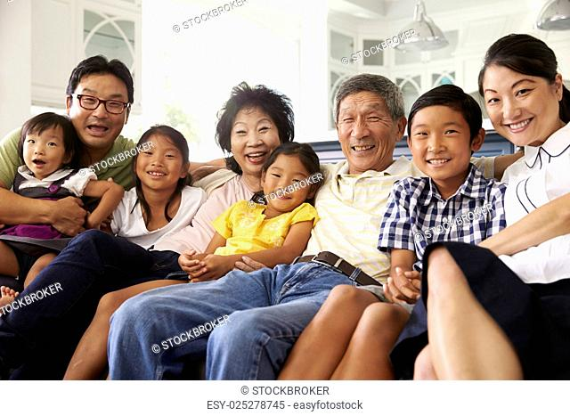Portrait Of Extended Family Group Sitting At Home On Sofa