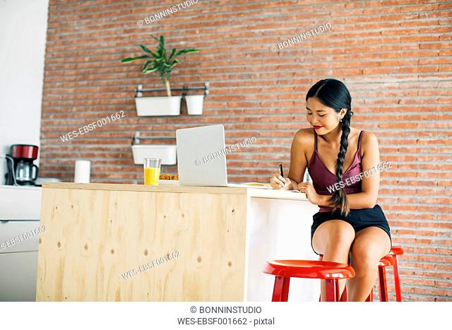 Woman working on kitchen counter at home