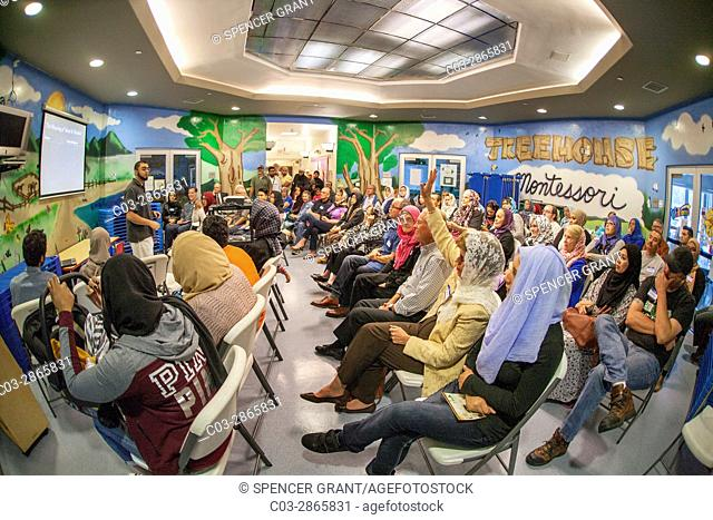 On visitors' day at an Anaheim, CA, mosque, a young Muslim man explains the Islamic religion to a non-Muslim audience using a computer monitor visual aid