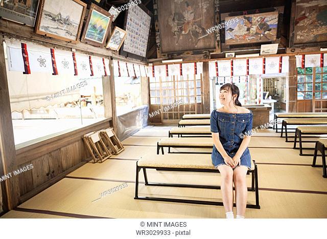 Young woman wearing blue dress sitting on bench at Shinto Sakurai Shrine, Fukuoka, Japan