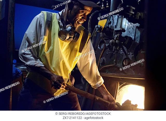 One of the railway workers of the Livingstone Express luxury train charcoal powered train locomotive. The train will stop on the bridge and allow passengers to...
