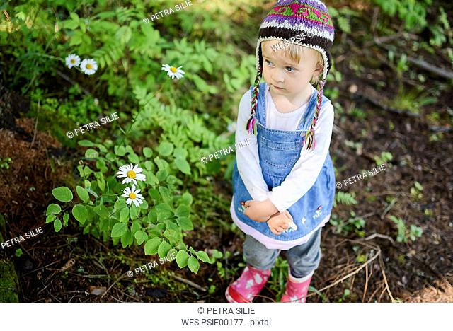 Portrait of sad little girl wearing knitted hat and denim dress outdoors