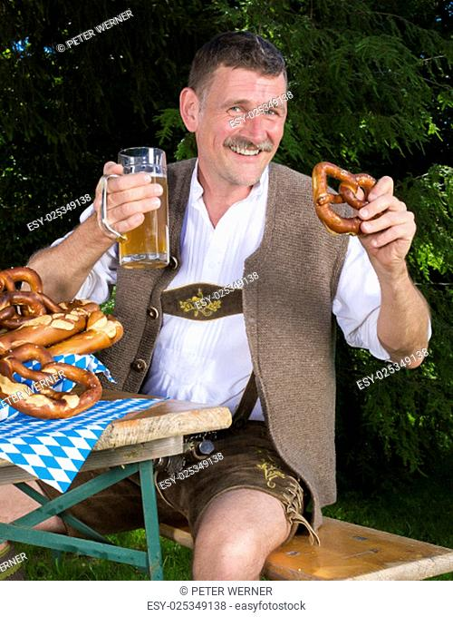 bavarian man sitting on bench with a beer mug and a pretzel