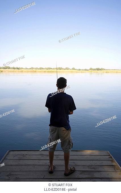 Young Man Fishing in the Zambezi River - Rear View  Lower Zambezi National Park, Southern Province, Zambezi