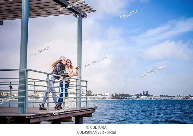 Two young women friends leaning on sea pier railings