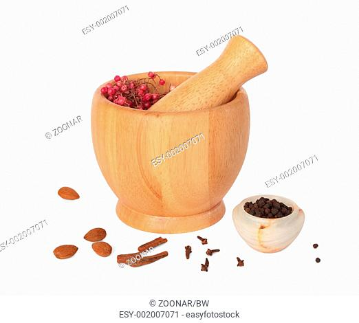 Wooden pestle and mortar with some spices on white