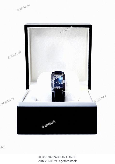 This photograph represent a black box with luxury platinum watch on white background