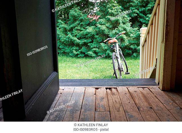 Open front door with bicycle in garden
