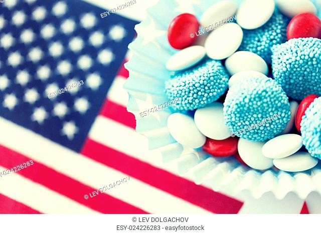 american independence day, celebration, patriotism and holidays concept - close up of glazed sweet candies with flag and paper stars decoration at 4th july...