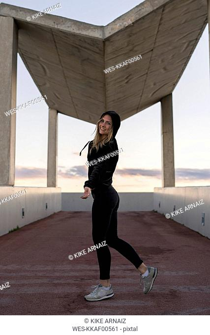 Spain, Barcelona, smiling young woman dressed in black