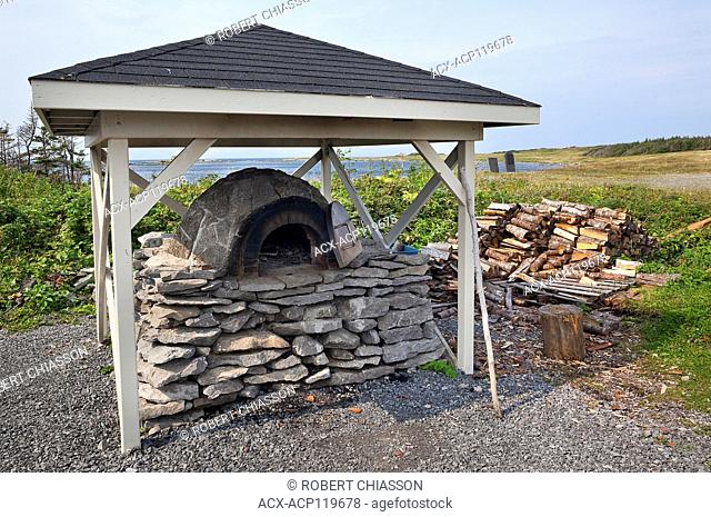 Outdoor, wood-fired, brick-and-stone bread oven on a stone base. The oven is used by Parks Canada interpreters to demonstrate traditional bread-baking...