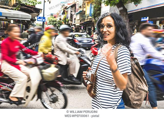 Vietnam, Hanoi, portrait of smiling young woman amidst traffic in the city