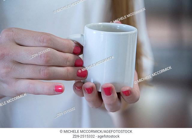 Closeup of a woman's hands holding coffee cup