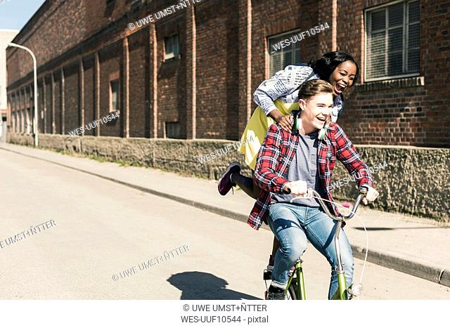 Young man riding bicycle with his girlfriend standing on rack