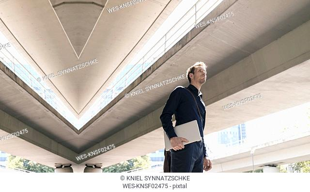 Businessman standing at underpass holding laptop, composite