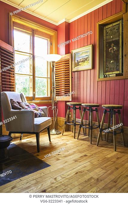 Grey upholstered sitting chair and wooden barstools in the dining room inside an old circa 1850 Canadiana cottage style home
