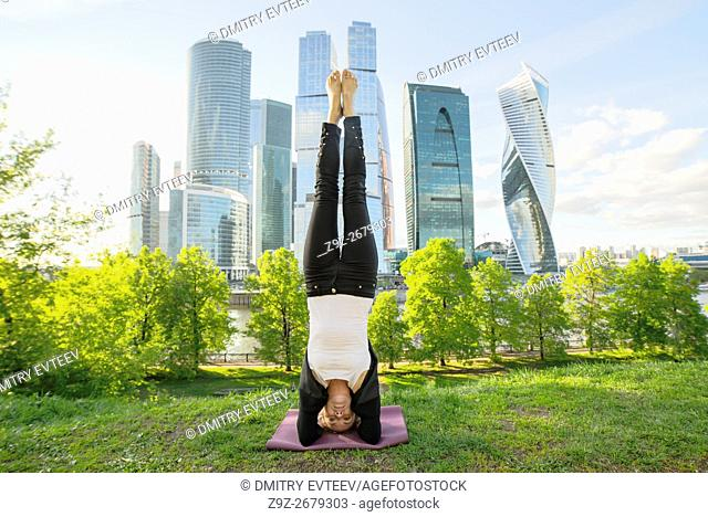 Yoga training as asana posture of young woman in business suit in Moscow