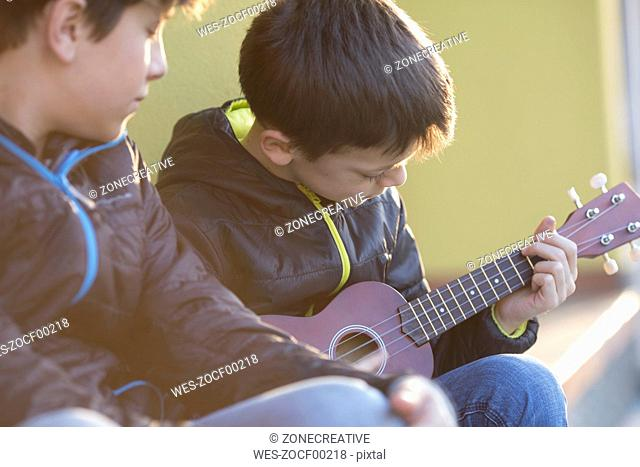 Boy playing ukulele while his friend watching him