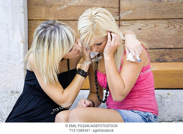 Two young women together one is crying