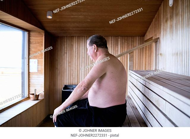 Mature man sitting in sauna