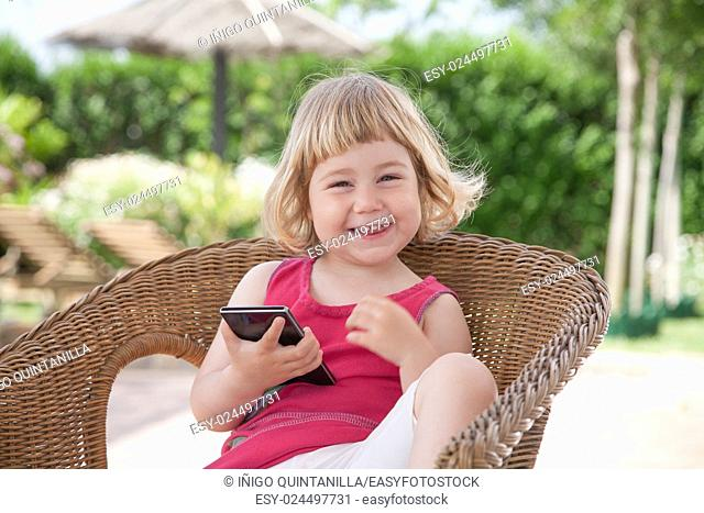 blonde caucasian girl two years old in summer red dress sitting on wicker chair with smartphone or mobile phone in hands looking and laughing