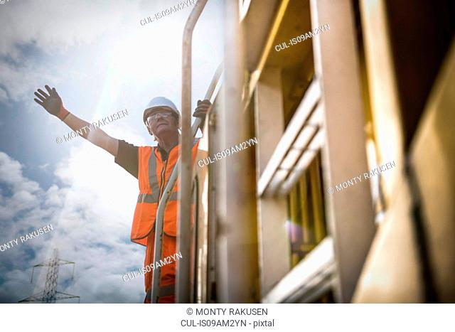 Railway worker signalling to train on railway, low angle view