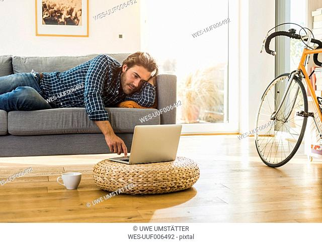 Young man lying on the couch at home