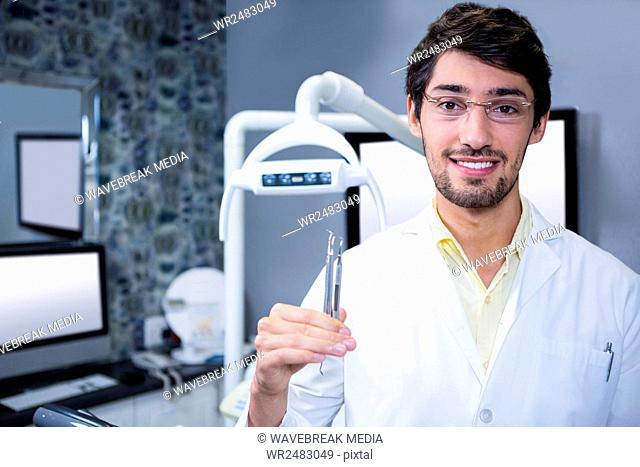 Portrait of smiling dentist standing with a dental tool