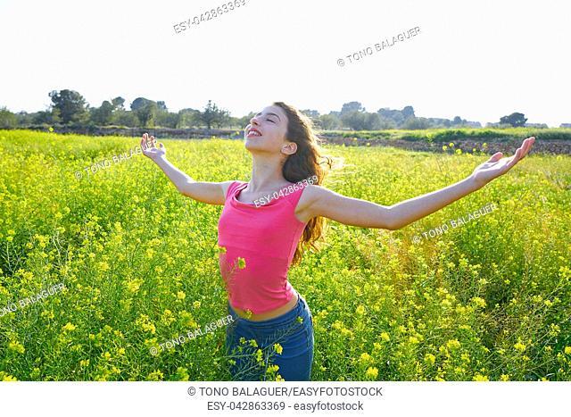 open arms happy teen girl in spring meadow brunette