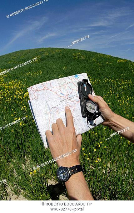 Man's hand holding compass and map
