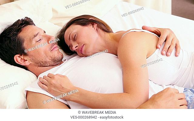 Affectionate couple sleeping on bed together
