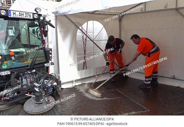 15 June 2019, Lower Saxony, Hanover: The still image from a video shows two men sweeping water from a tent of an art exhibition in front of the market church...