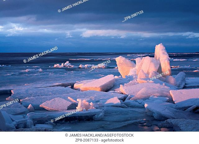 Ice breaking up on Lake Simcoe bathed in the beautiful glow of sunset. Jackson's Point, Lake simcoe, Ontario, Canada