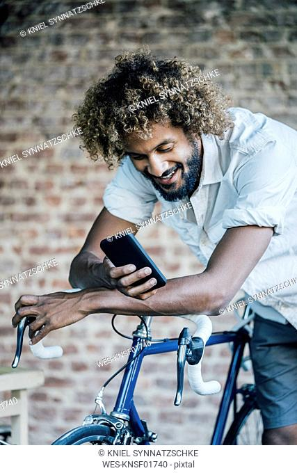 Happy young man with bicycle checking cell phone