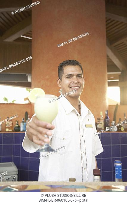 Hispanic male bartender offering up a pina colada, Los Cabos, Mexico