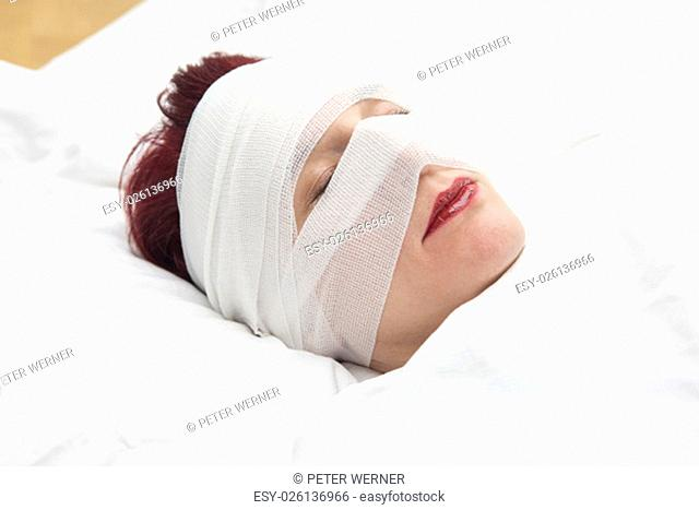 closeup of beautiful woman in bed with bandages wrapped around her head