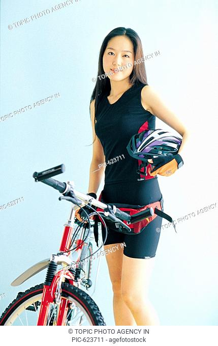 A Model Holding a helmet Standing Next to a Bicycle