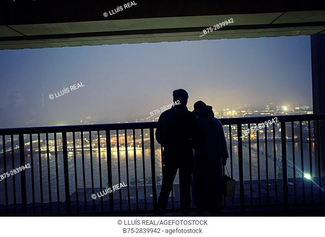 Silhouettes of young couple looking at the City from a balcony at dusk. Tate Modern, The City, Bankside, London, UK