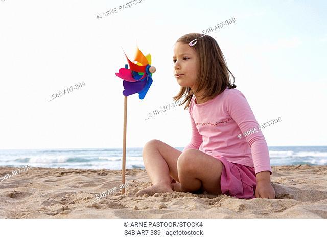 Girl with pinwheel on the beach, Odeceixe, Algarve, Portugal
