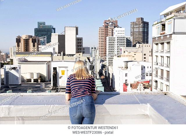 Young woman looking from a rooftop terrace, rear view