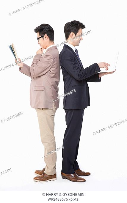 Side view of businessman reading a book and another using a notebook computer standing back to back