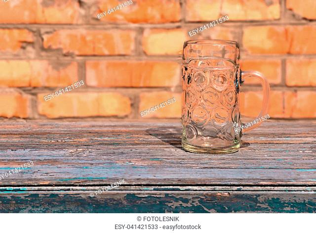 large beer glass mug, standing on an old table on a brick wall background