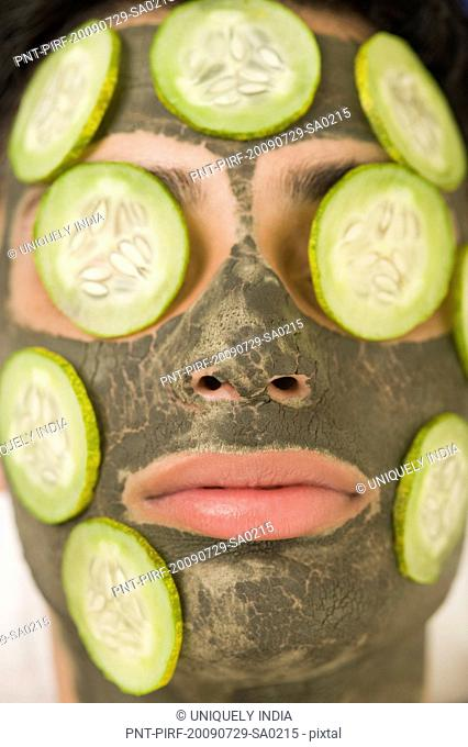 Close-up of a man with mud pack and cucumber slices on face