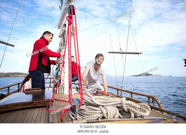 Man on sailboat uses cable winch to hoist a load