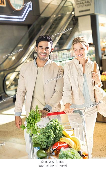Portrait smiling young couple with shopping cart grocery shopping in market