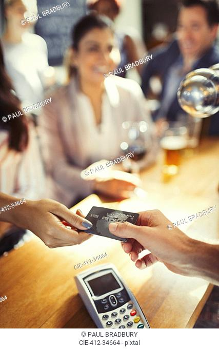 Woman paying bartender with credit card at bar